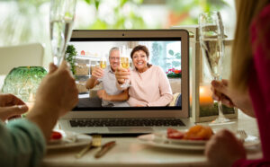 Man and woman sitting at the dining table, having dinner, drinking Champagne and having video call with senior parents on laptop. Staying home, quarantine and social distancing celebration of event.
