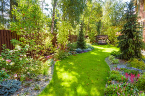 Landscaping in green home garden. Landscape design with plants and flowers at residential house. Scenic view of nice landscaped garden in backyard. Scenery of natural landscaping place in summer.