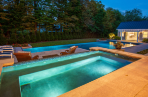 Outdoor pool with lights at night next to pool house