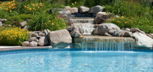 A swimming pool and waterfall by Ambrosio Landscape Solutions