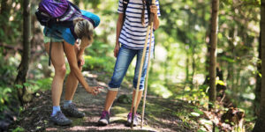 Mother and daughter hiking in forest. Mother is applying tick repellent on the daughter's legs.