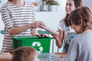 Close-up of mother teaching kids how to segregating waste at home