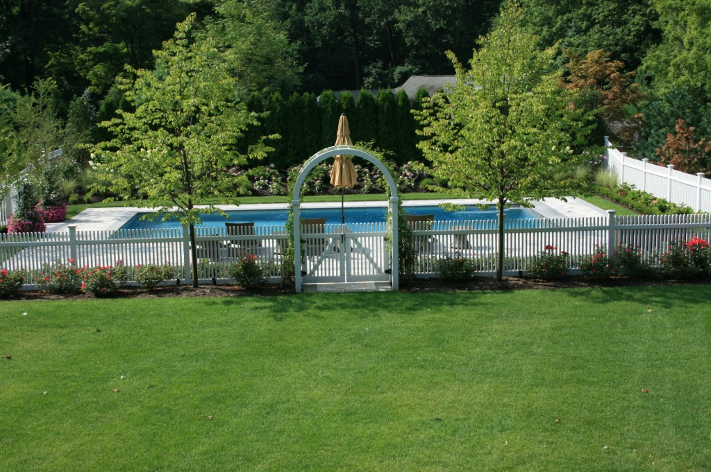 White fence with gate around pool
