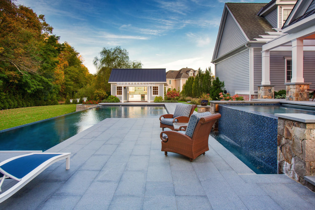 Waterfall and pool next to stone patio