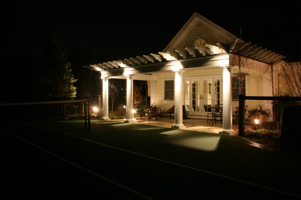 Columns of pool house lit up at night by lights