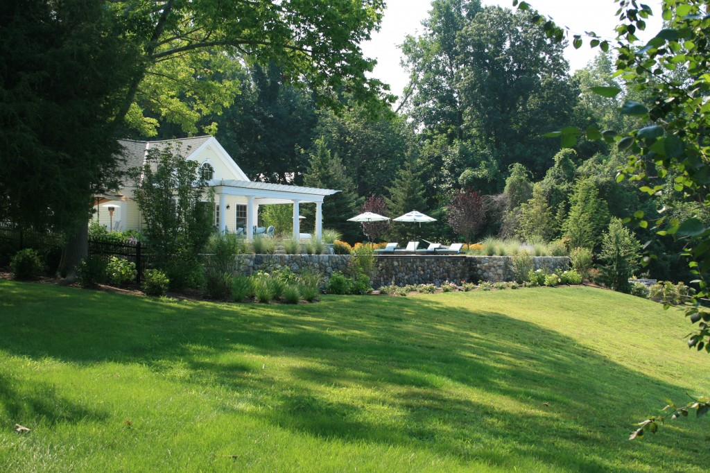 Large lawn in front of stone retaining wall