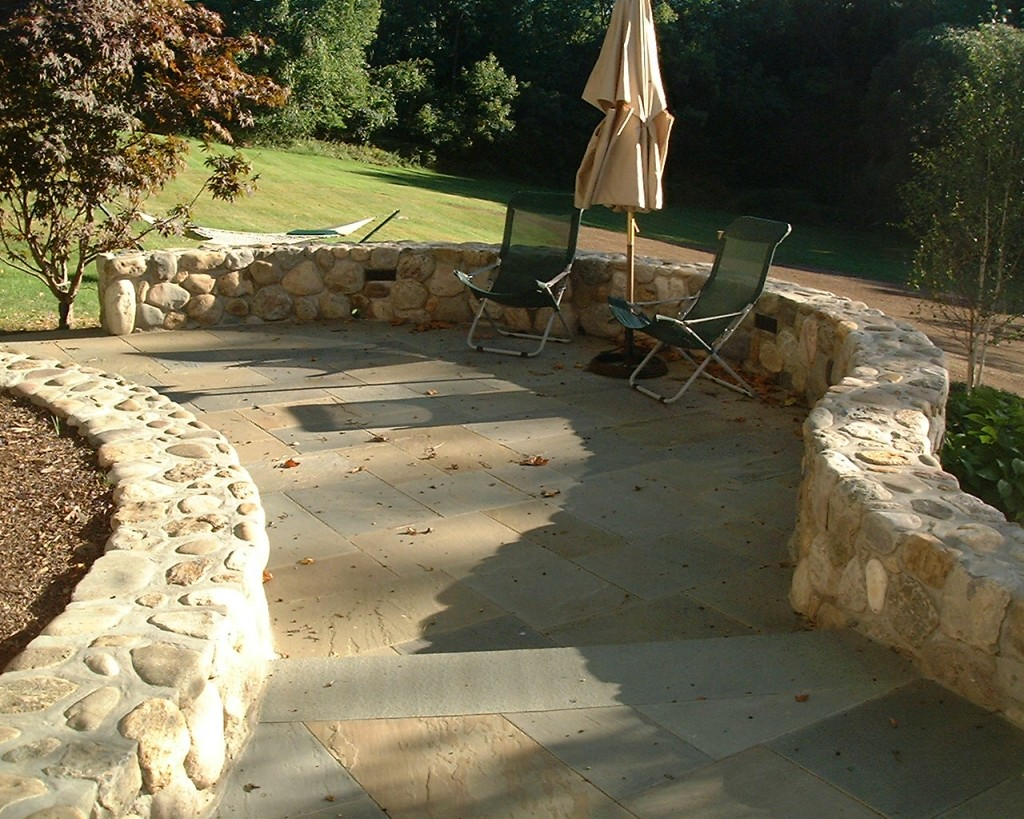 Stone walls and patio with green folding chairs