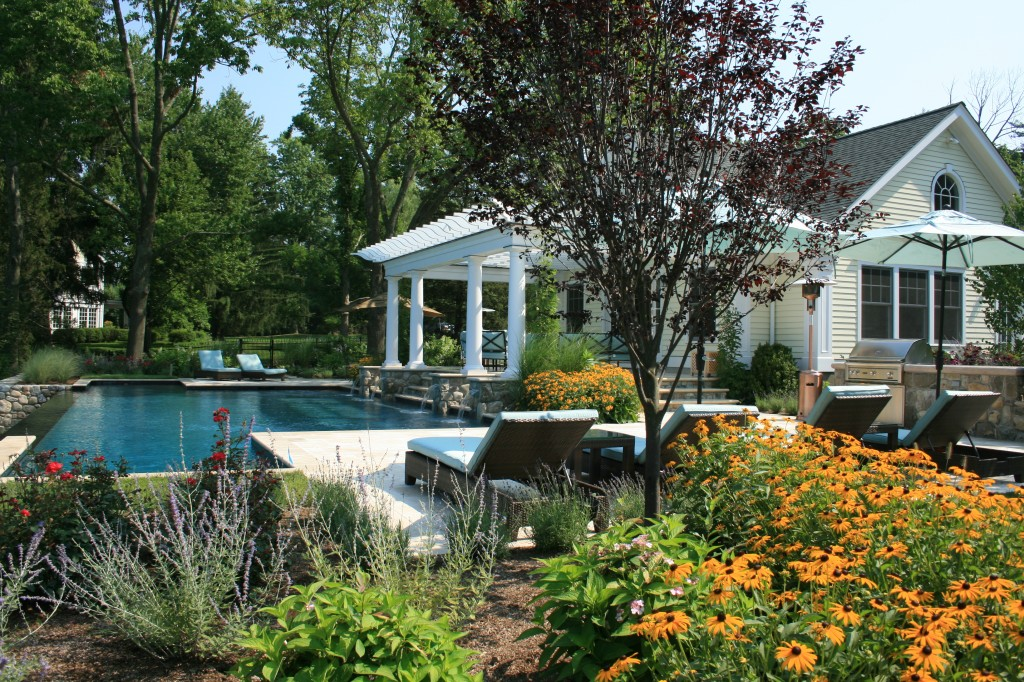Pool and pool house with beautiful landscaping