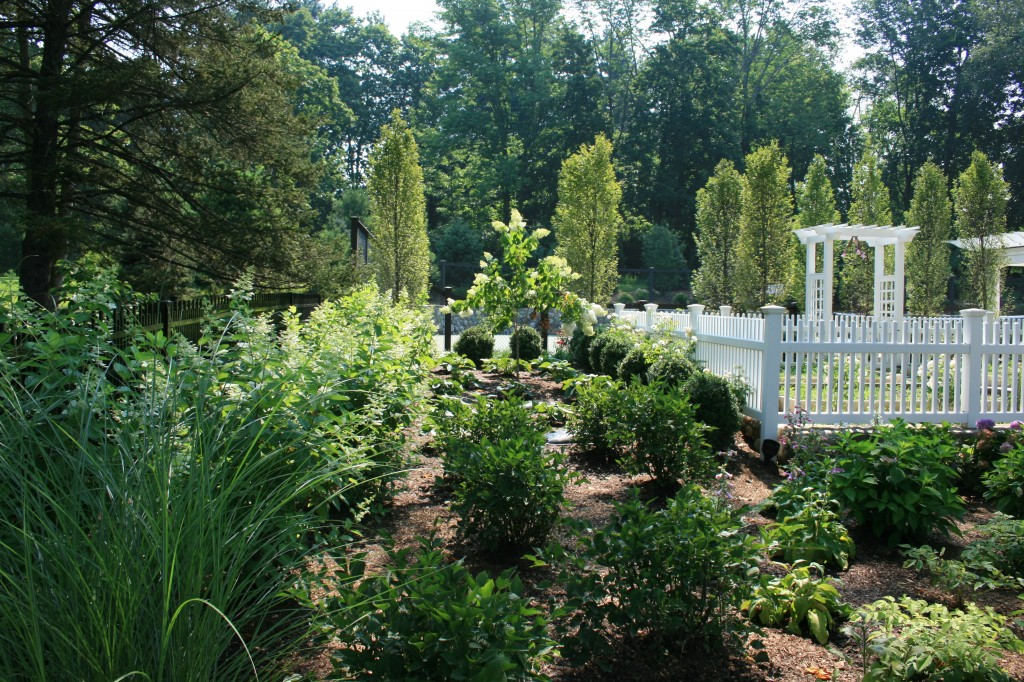 Large garden behind white fence