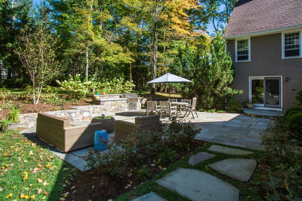 Stone patio with seating and grill