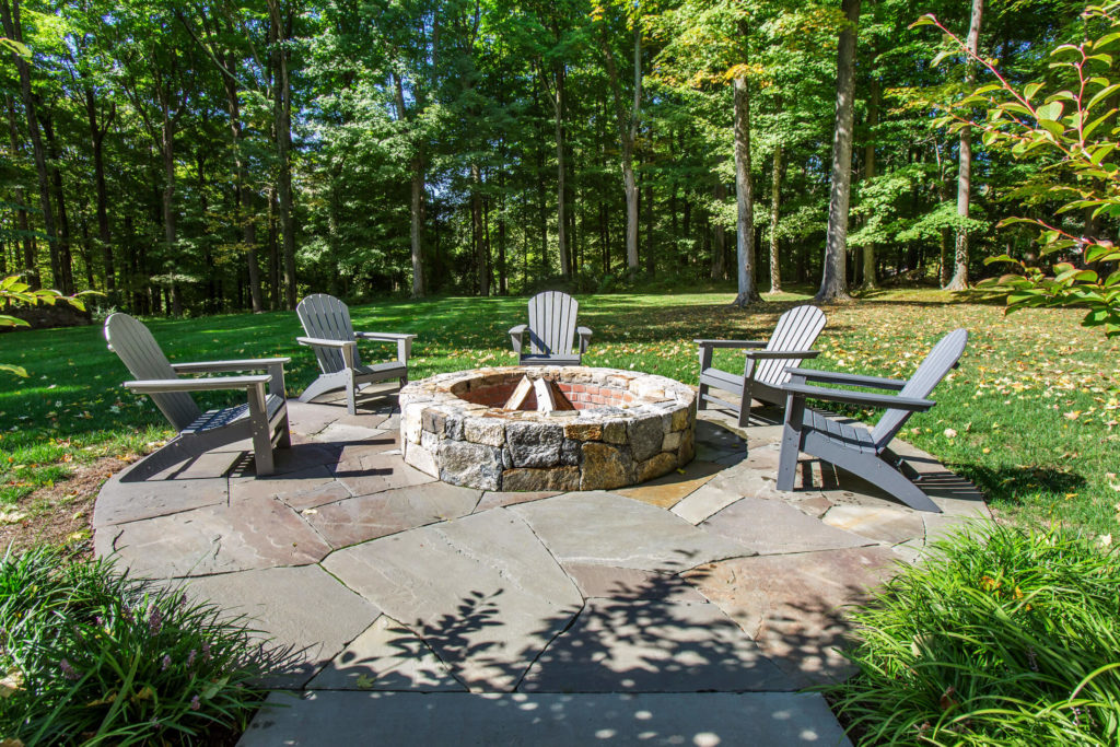 Stone fire pit with gray lawn chairs around