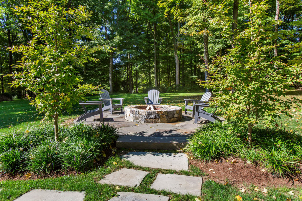 Stone fire pit with lawn chairs around