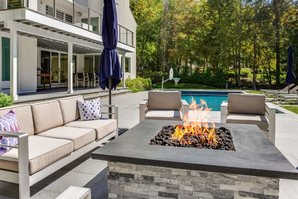 Outdoor seating area with fire pit and pool in background