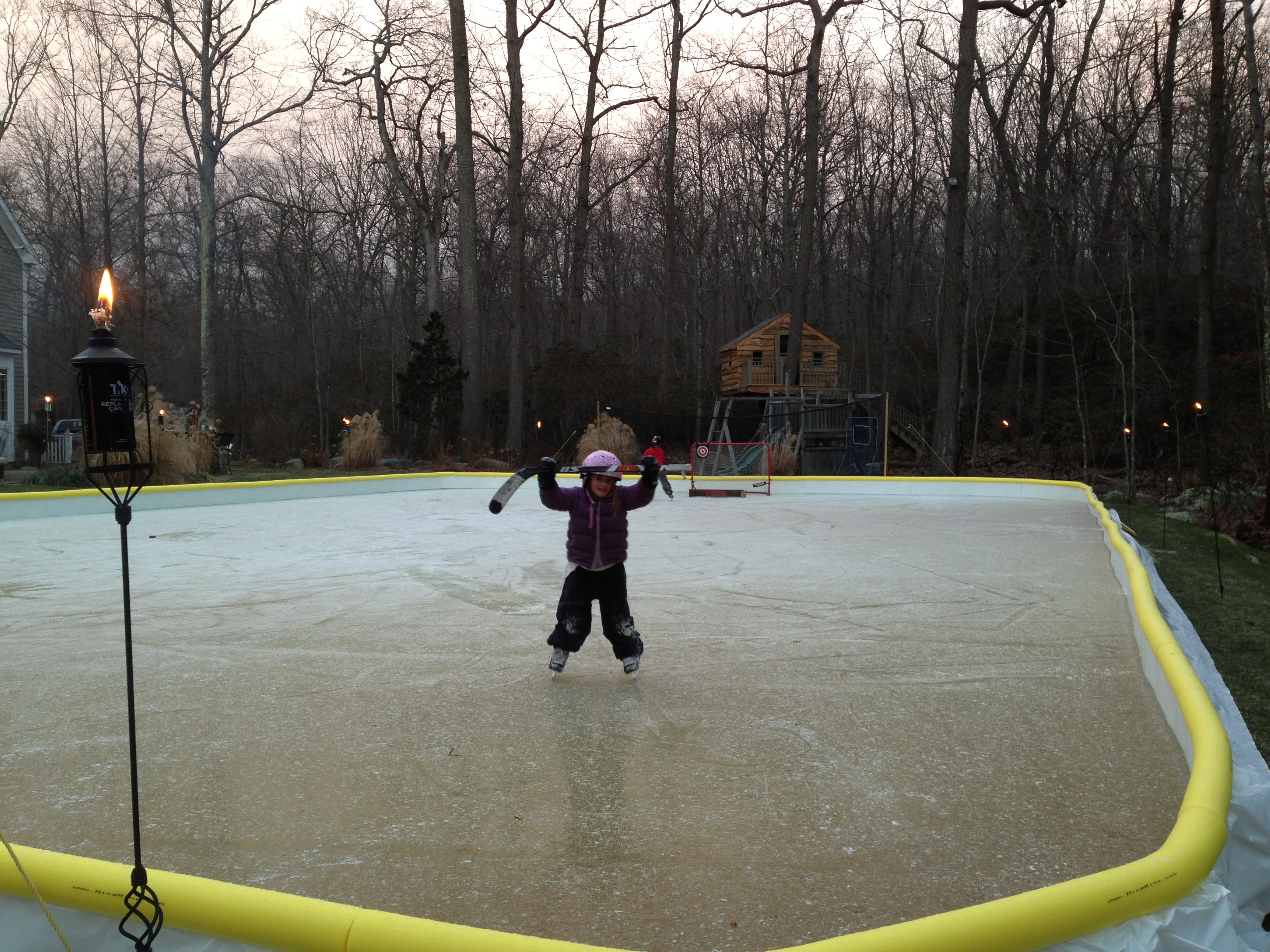 Girl holding up hockey stick on backyard ice rink