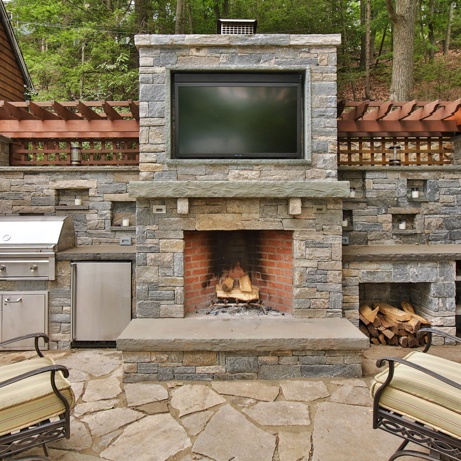 Outdoor fireplace with TV above and grill next to