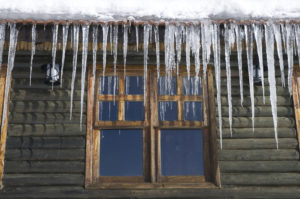 Icicles forming on log cabin roof