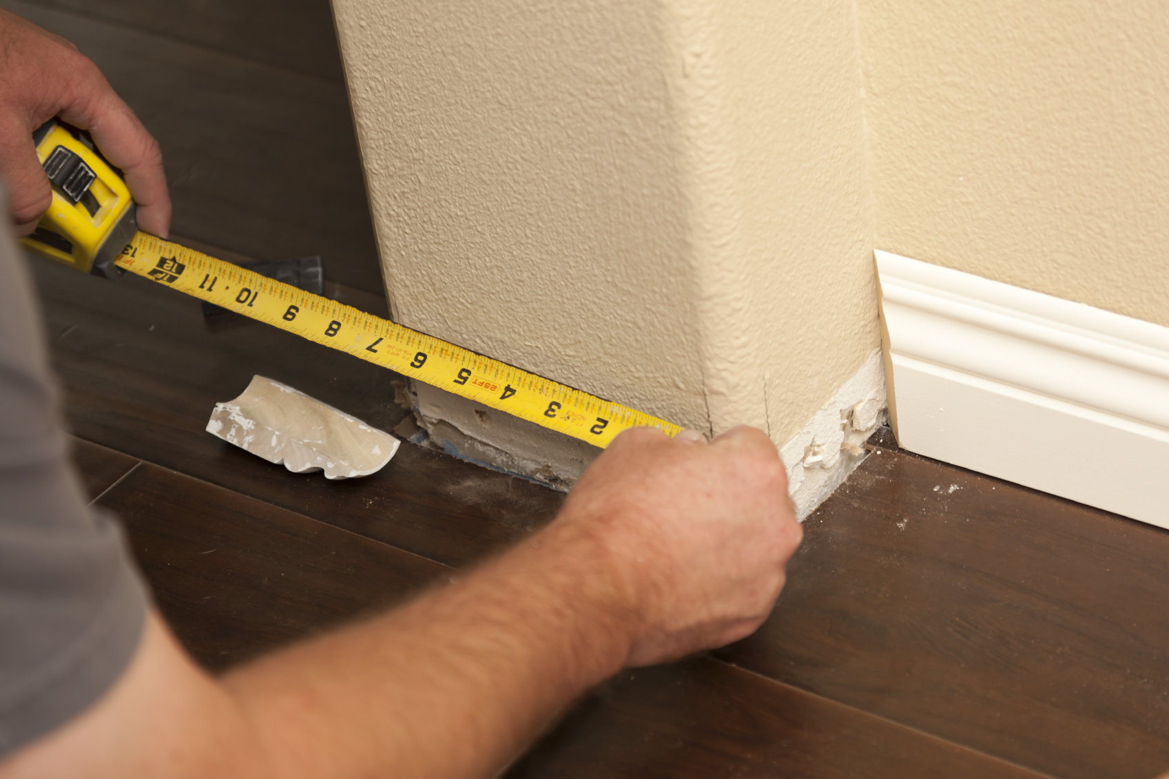 Contractor Measuring For New Baseboard With Bull Nose Corners And Laminate Flooring Abstract