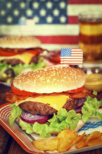 Large cheese burger on platter with american flag on top