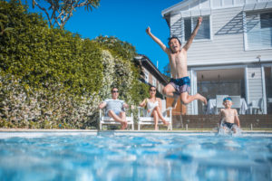 kid jumping into a swimming pool outside
