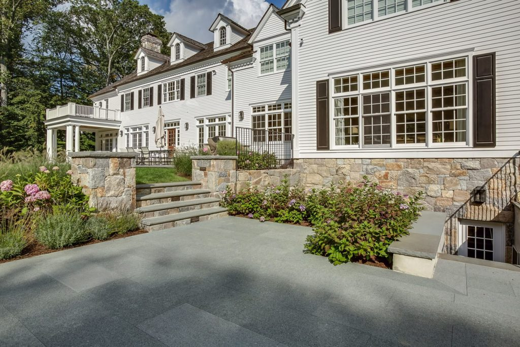 Stone patio with stairs to lawn