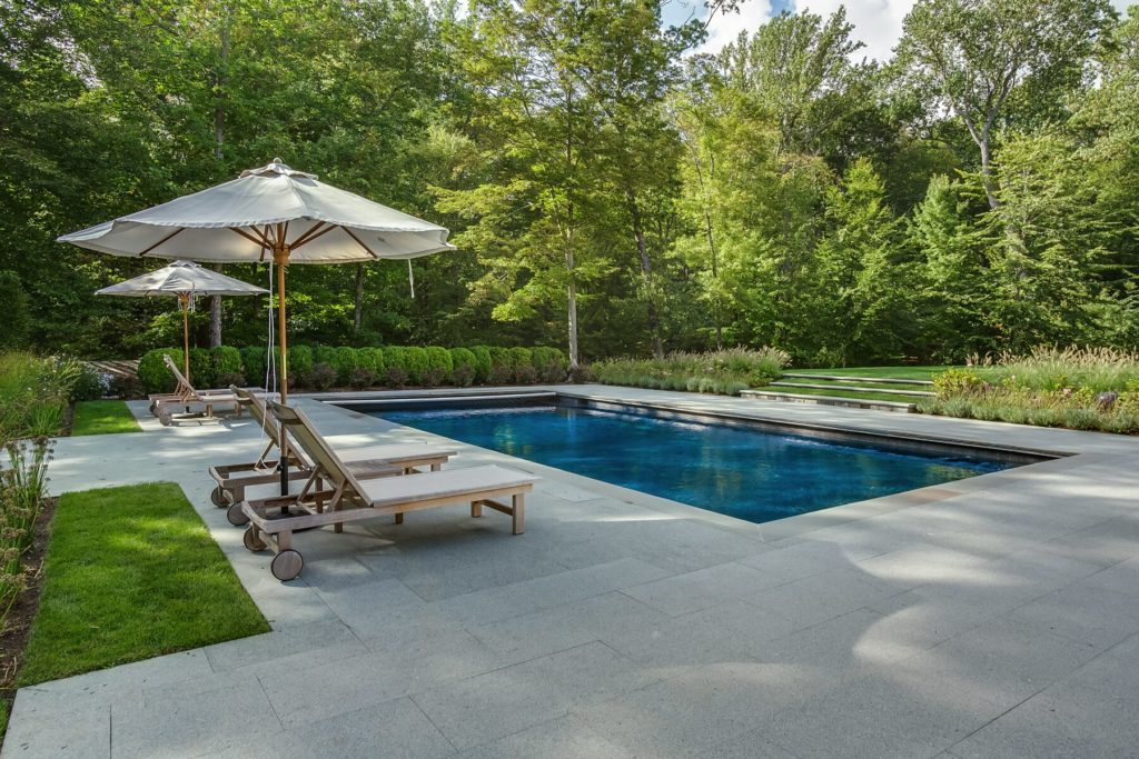 Pool with stone patio and lounge chairs surrounding it