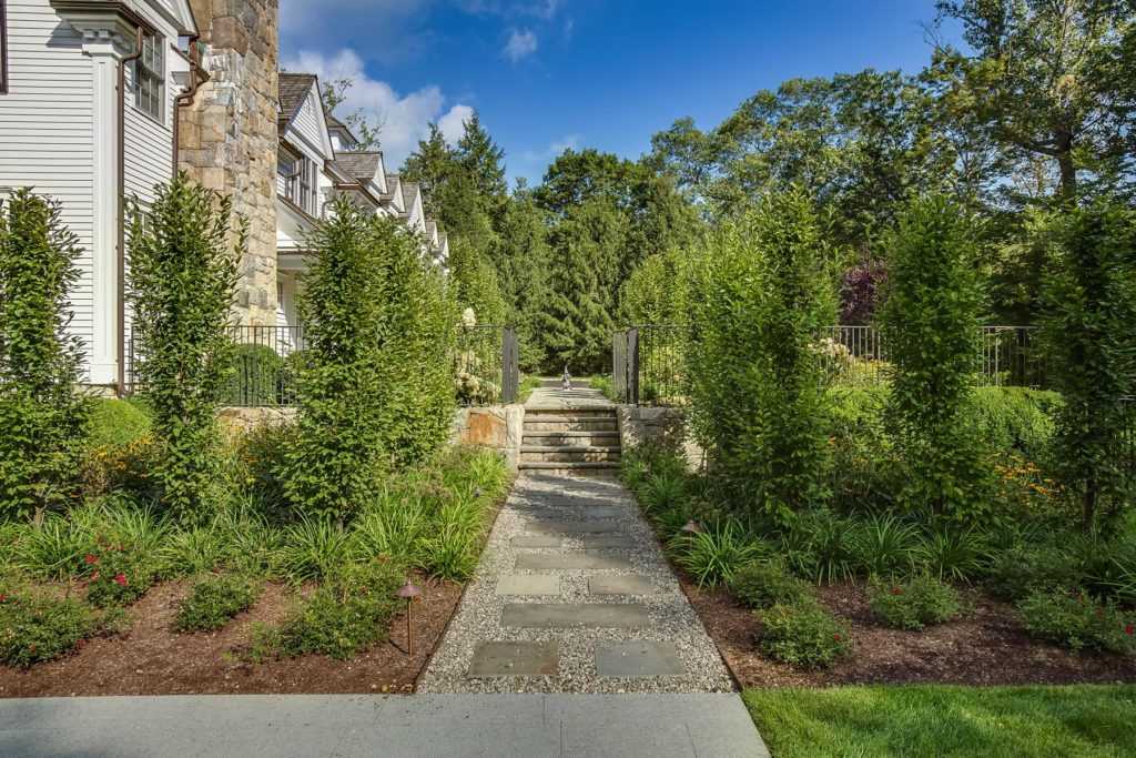 Stone walkway next to trees leads to house