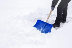 Man shoveling mound of snow
