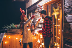 Woman stringing holiday lights with husband
